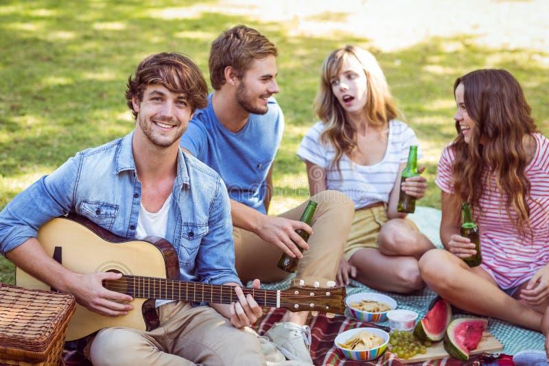 Gelukkige vrienden in het park die picknick hebben royalty-vrije stock afbeelding