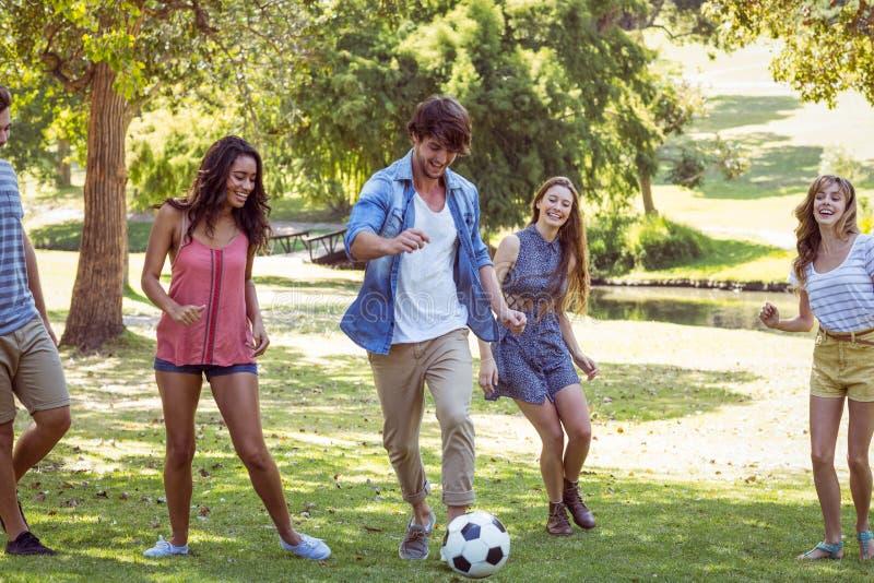 Gelukkige vrienden in het park met voetbal stock foto's