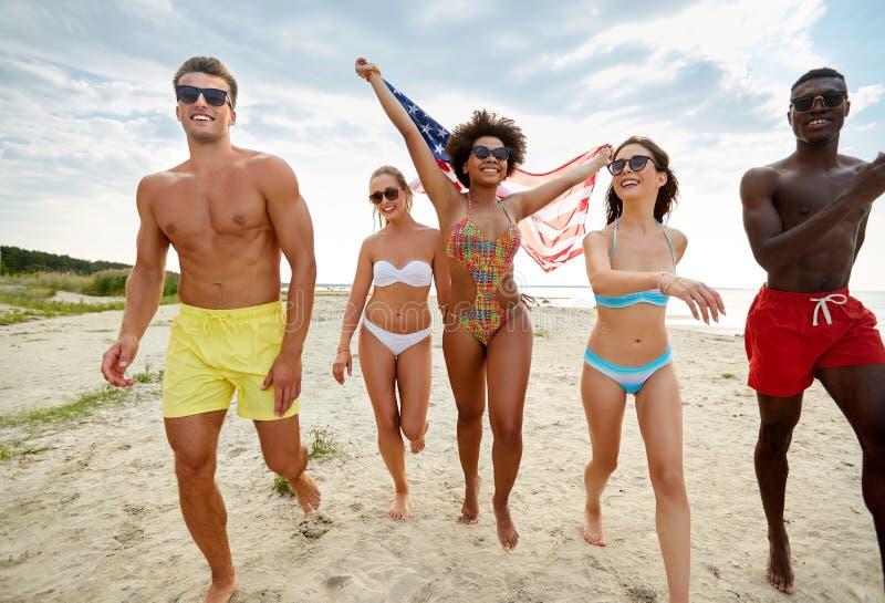 Gelukkige vrienden met Amerikaanse vlag op de zomerstrand stock foto's