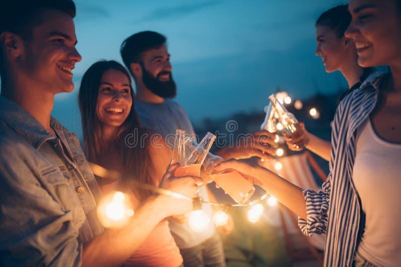 Gelukkige vrienden met dranken die bij dakpartij bij nacht roosteren royalty-vrije stock foto
