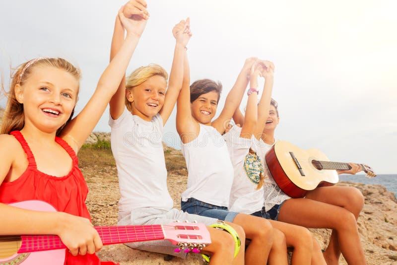 Gelukkige vrienden met gitaar die pret op het strand hebben stock afbeelding