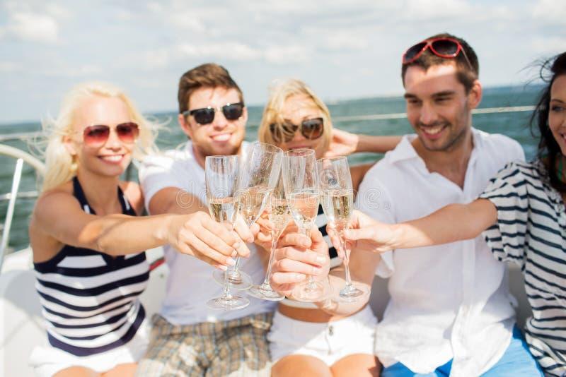 Gelukkige vrienden met glazen champagne op jacht stock afbeeldingen