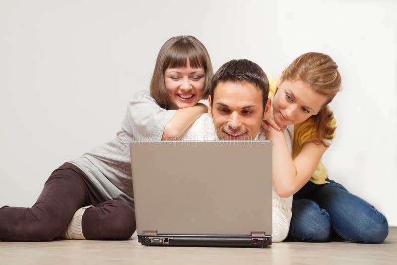 Gelukkige vrienden met laptop computer stock afbeeldingen