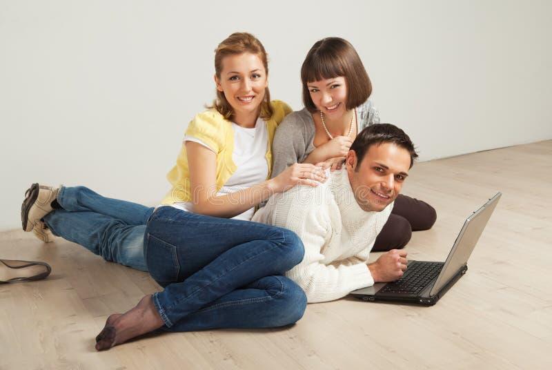 Gelukkige vrienden met laptop computer stock afbeelding