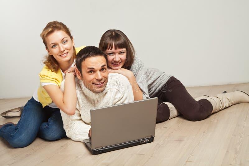Gelukkige vrienden met laptop computer royalty-vrije stock afbeeldingen
