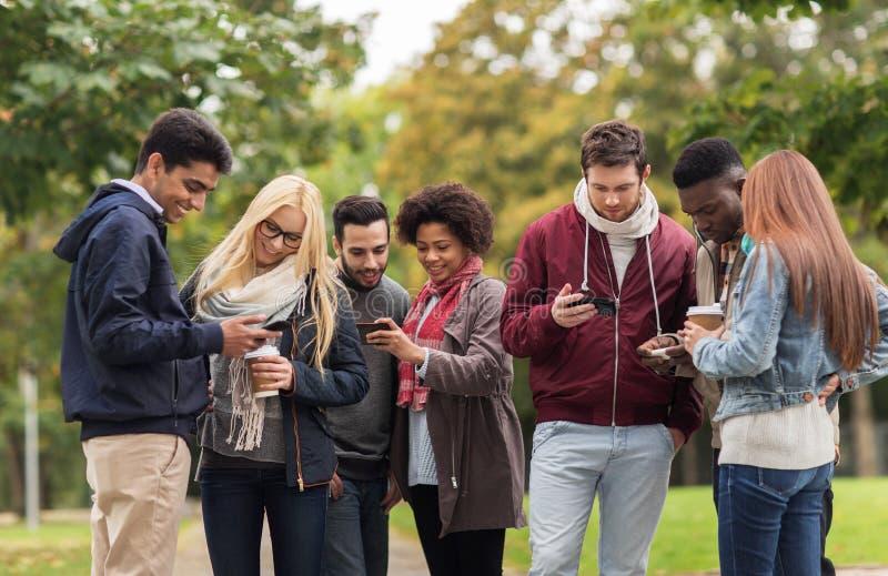 Gelukkige vrienden met smartphone en koffie in openlucht stock foto's