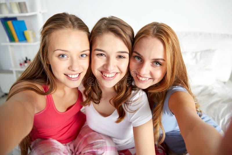 Gelukkige vrienden of tienermeisjes die selfie thuis nemen stock foto