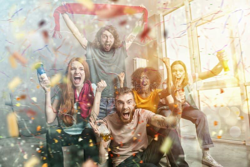 Gelukkige vrienden van voetbalventilators die op voetbal op TV letten en overwinning met dalende confettien vieren royalty-vrije stock foto's