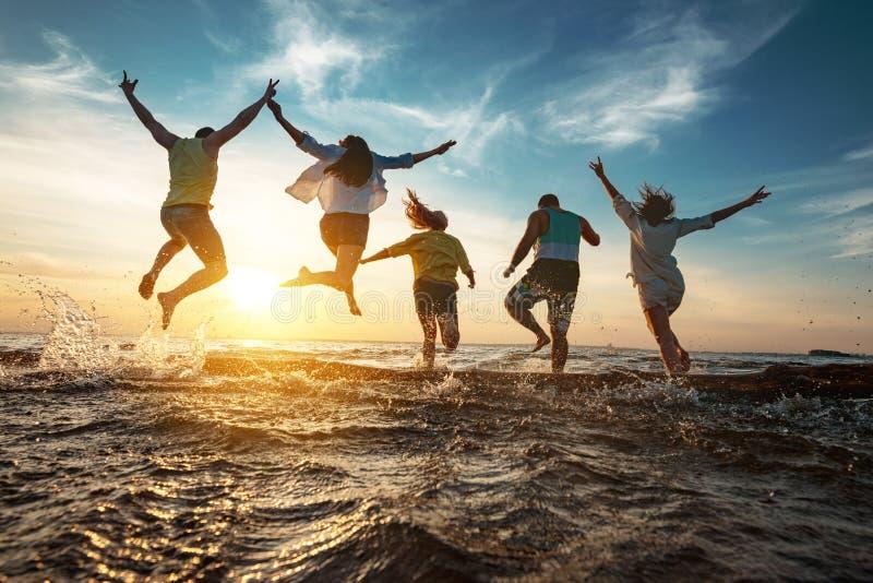 Gelukkige vriendenlooppas aan zonsondergangmeer na partij stock afbeelding