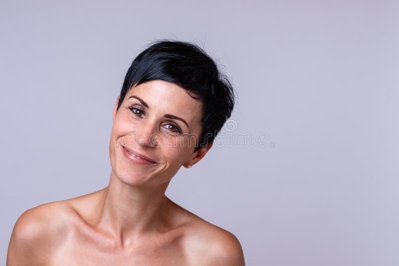 Gelukkige vriendschappelijke jonge vrouw met naakte schouders stock foto