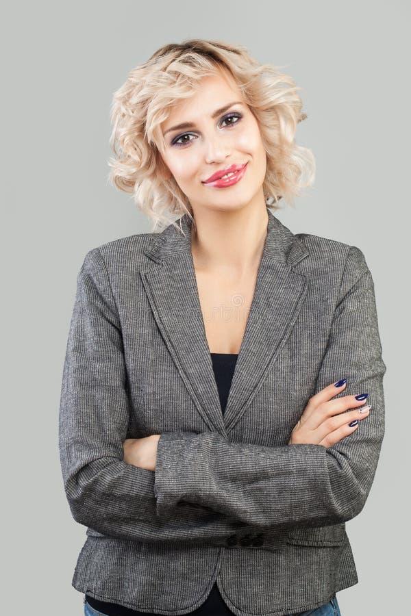 Gelukkige vriendschappelijke vrouw die en zich met gekruist wapensportret glimlachen bevinden Slimme onderneemster in kostuumport stock foto