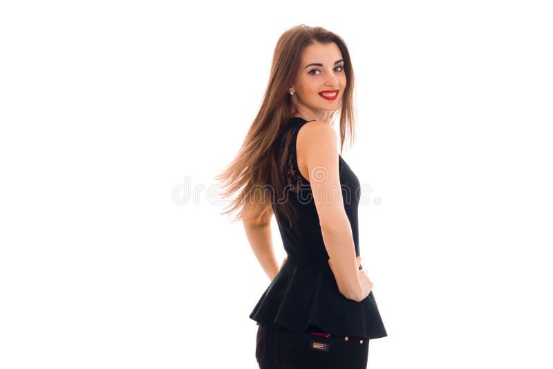 Gelukkige vrij donkerbruine vrouw in zwarte kleding met rode lippen die en op camera kijken glimlachen die op witte achtergrond w royalty-vrije stock afbeeldingen