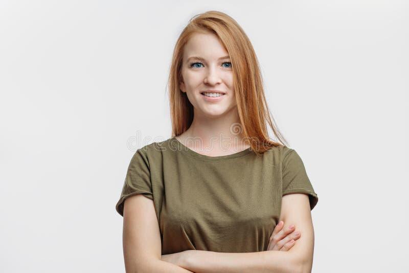 Gelukkige vrij jonge dame met rood haar die zich met gekruiste wapens bevinden royalty-vrije stock fotografie