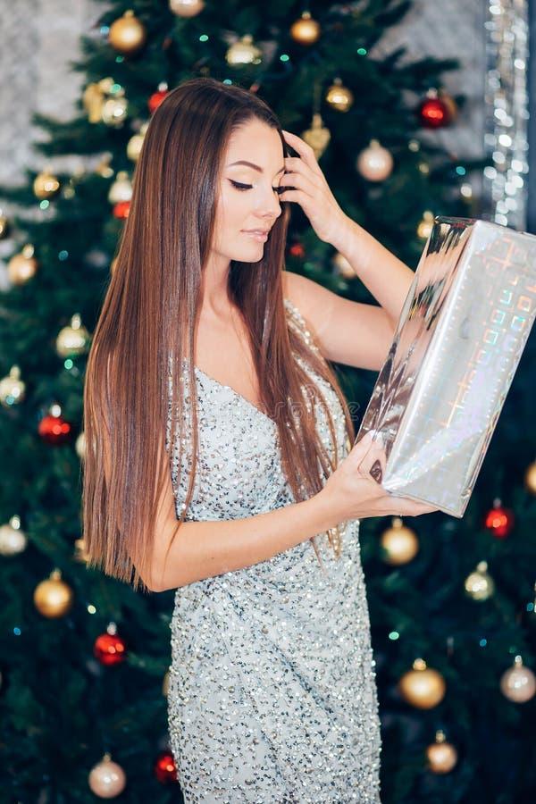 Gelukkige vrij jonge de giftdoos van de vrouwenholding dichtbij Kerstmisboom stock afbeeldingen