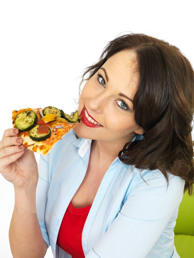 Gelukkige vrij Jonge Vrouw die een Plak van vers Gebakken Vegetarische Pizza eten stock foto's