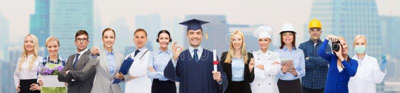 Gelukkige vrijgezel met diploma over beroeps stock foto
