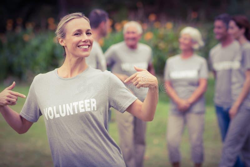 Gelukkige vrijwilliger die haar t-shirt tonen aan camera stock afbeeldingen