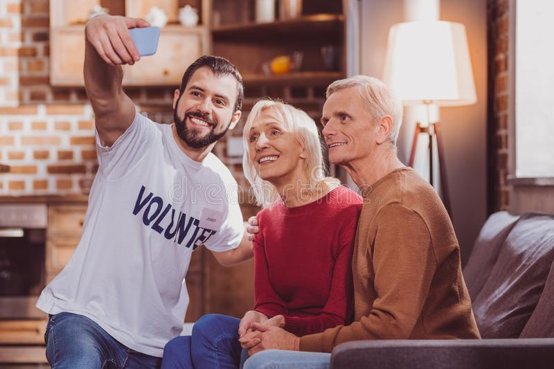 Gelukkige vrijwilliger selfies met gepensioneerden stock fotografie