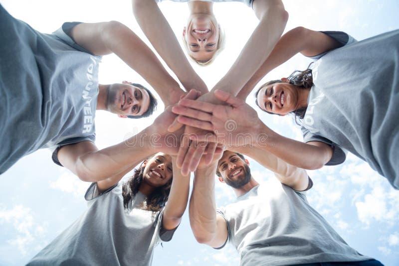 Gelukkige vrijwilligers die hun handen samenbrengen royalty-vrije stock afbeelding