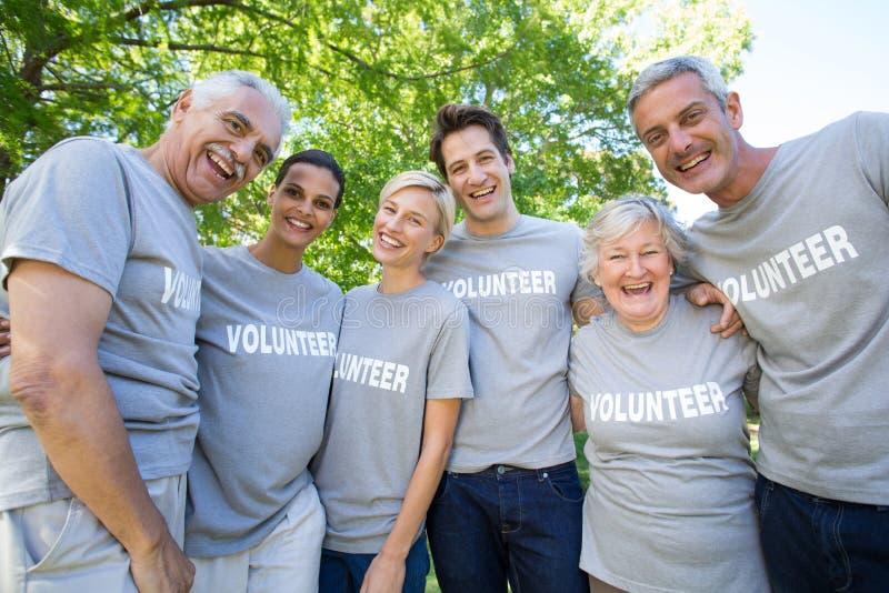 Gelukkige vrijwilligersfamilie die bij de camera glimlachen royalty-vrije stock afbeeldingen