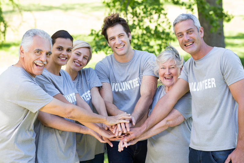 Gelukkige vrijwilligersfamilie die hun handen samenbrengen stock foto's