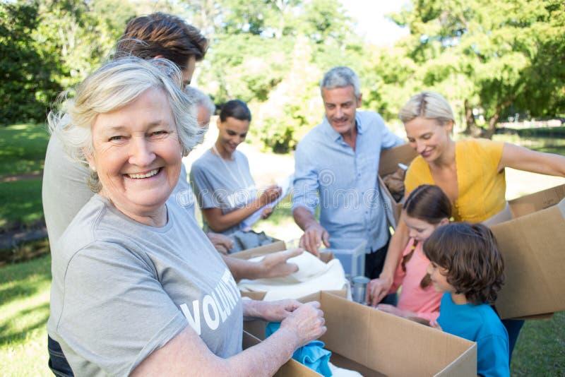 Gelukkige vrijwilligersfamilie die schenkingenmaterialen scheiden stock foto