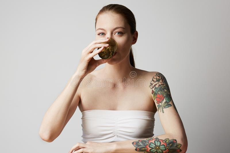 Gelukkige vrolijk tattoed jonge vrouw die haar rood haar dragen bekijkend camera met blije en charmante glimlach stock fotografie