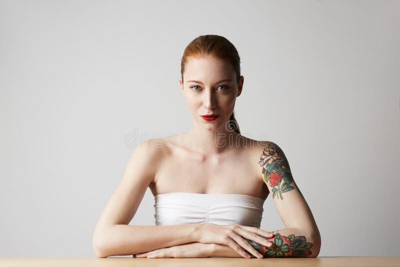 Gelukkige vrolijk tattoed jonge vrouw die haar rood haar dragen bekijkend camera met blije en charmante glimlach royalty-vrije stock afbeelding