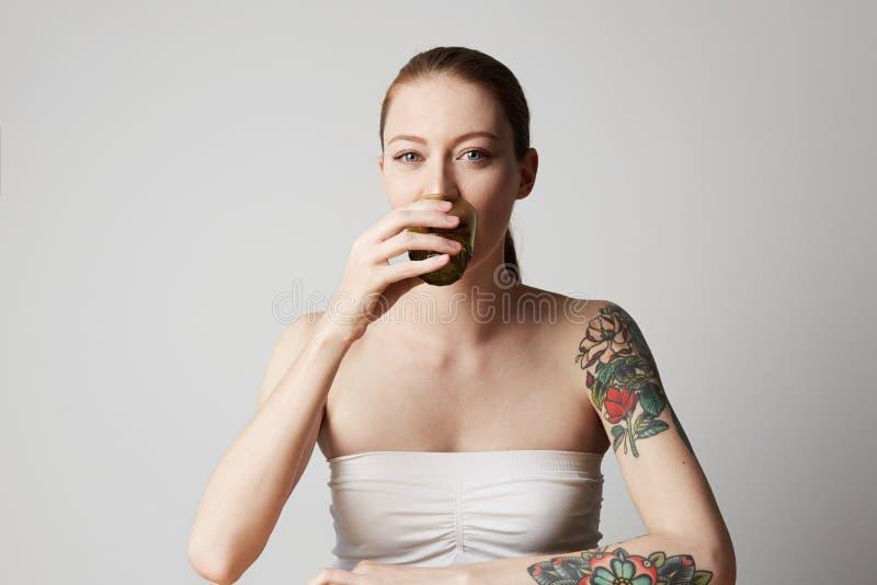 Gelukkige vrolijk tattoed jonge vrouw die haar rood haar dragen bekijkend camera met blije en charmante glimlach royalty-vrije stock foto