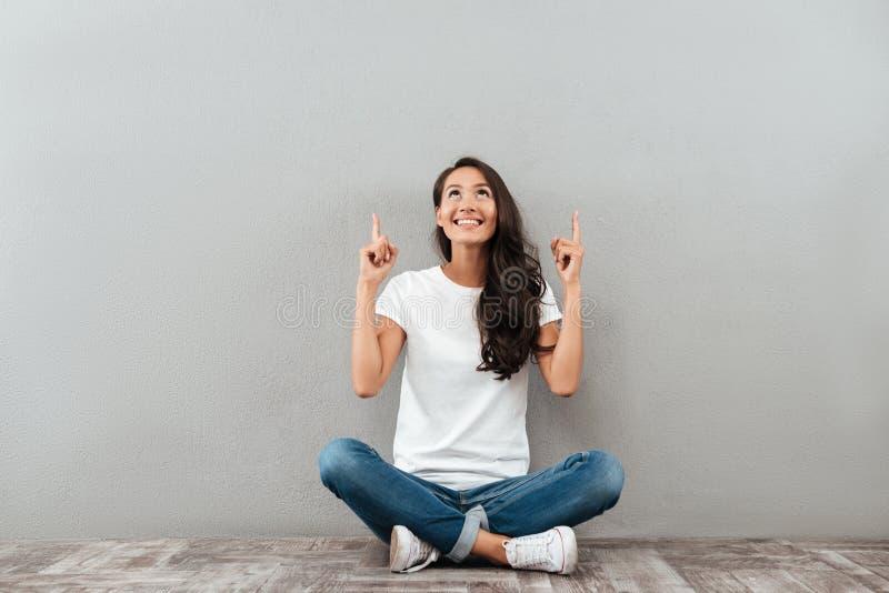 Gelukkige vrolijke Aziatische vrouwenzitting op de vloer stock foto's