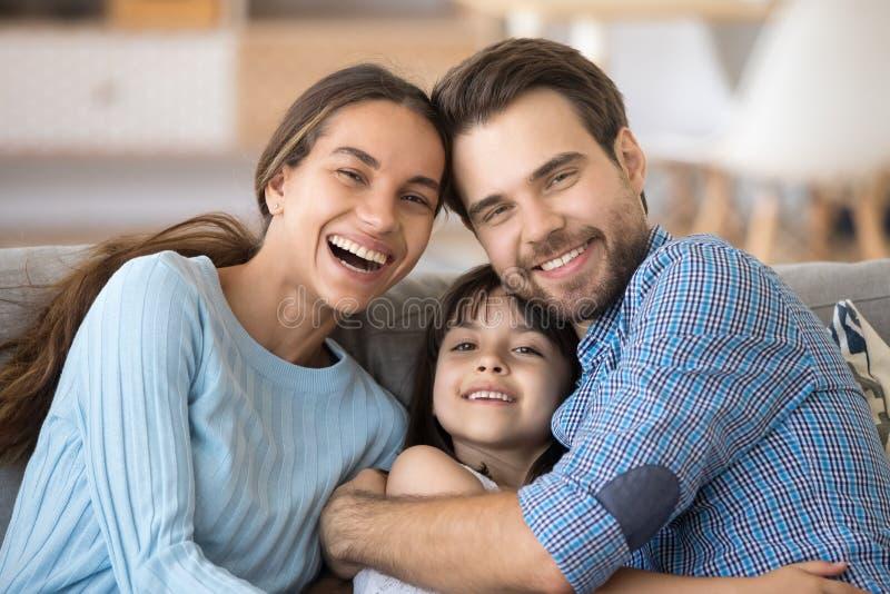 Gelukkige vrolijke familie die zitting op laag thuis omhelzen royalty-vrije stock foto's
