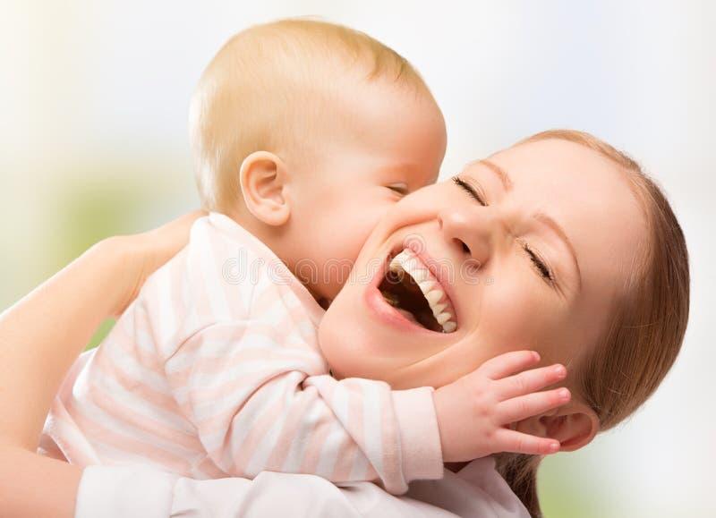 Gelukkige vrolijke familie. Het kussen van de moeder en van de baby stock afbeelding