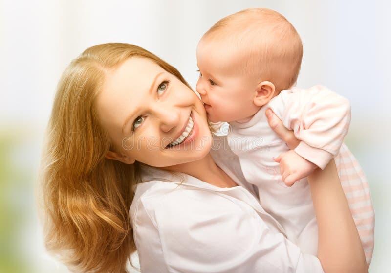 Gelukkige vrolijke familie. Het kussen van de moeder en van de baby stock foto's