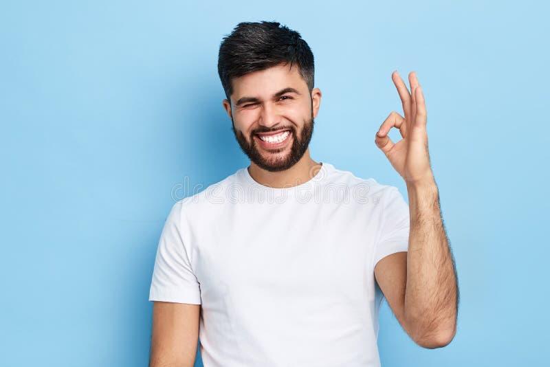 Gelukkige vrolijke gebaarde mens die zijn oog en o.k. teken tonen knipogen stock fotografie
