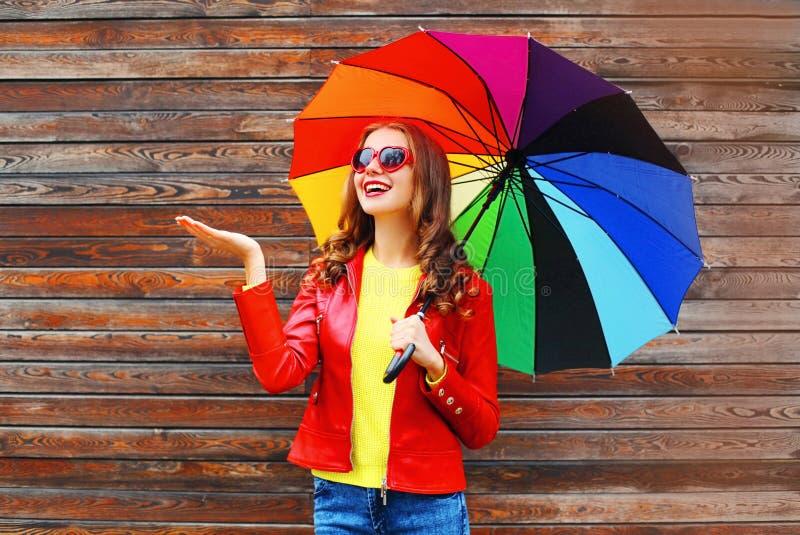 Gelukkige vrolijke glimlachende vrouw met kleurrijke paraplu in de herfstdag over houten achtergrond die rood leerjasje dragen stock foto's
