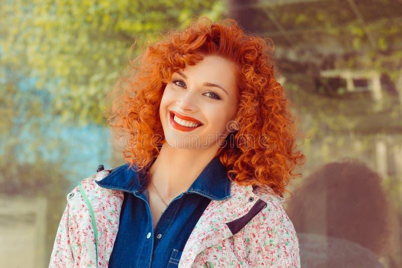Gelukkige vrolijke jonge vrouw die met het krullende haar van de roodharigegember zich bij positief nieuws verheugen royalty-vrije stock afbeelding