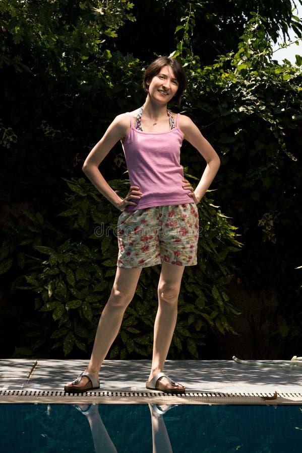 Gelukkige vrolijke jonge vrouw die zich in de tuin dichtbij het zwembad bevinden stock foto