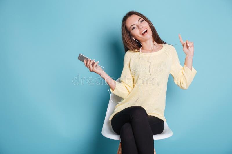 Gelukkige vrolijke meisje het luisteren muziek over blauwe achtergrond stock foto's