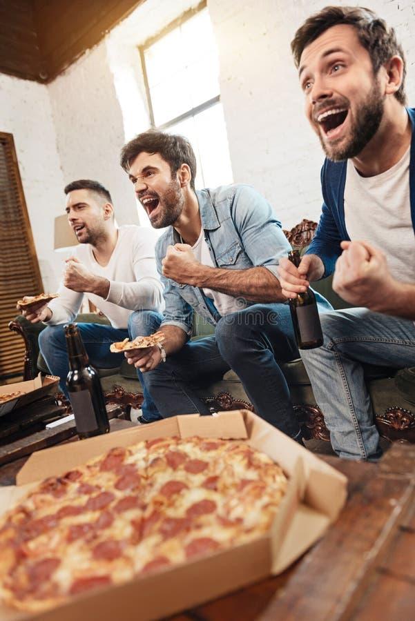 Gelukkige vrolijke mensen die op een voetbalspel letten stock afbeeldingen