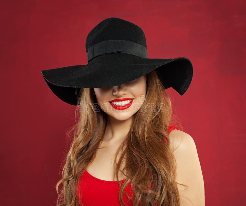 Gelukkige vrolijke modelvrouw in zwarte hoed op rode achtergrond Het glimlachen meisjesportret stock afbeelding