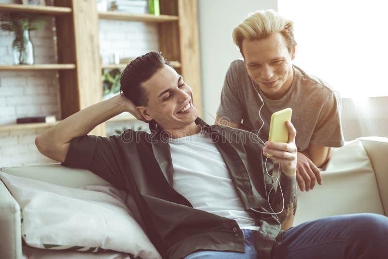 Gelukkige vrolijke paar het letten op film op smartphone royalty-vrije stock foto's