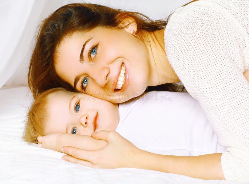 Gelukkige vrolijke portretmoeder en baby in bed stock foto