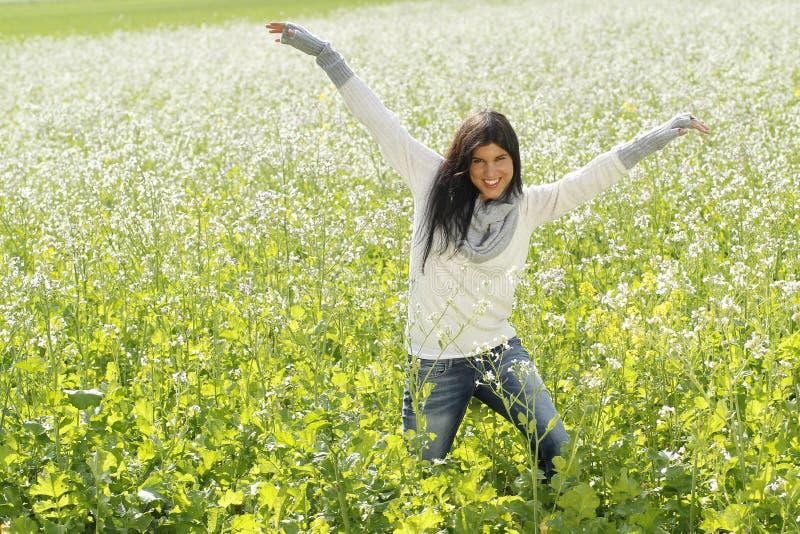 Gelukkige vrouw in aard met uitgestrekte wapens op een bloemgebied stock foto