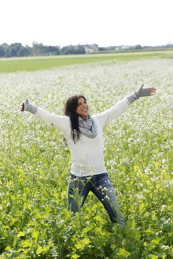 Gelukkige vrouw in aard met uitgestrekte wapens op een bloemgebied stock afbeeldingen