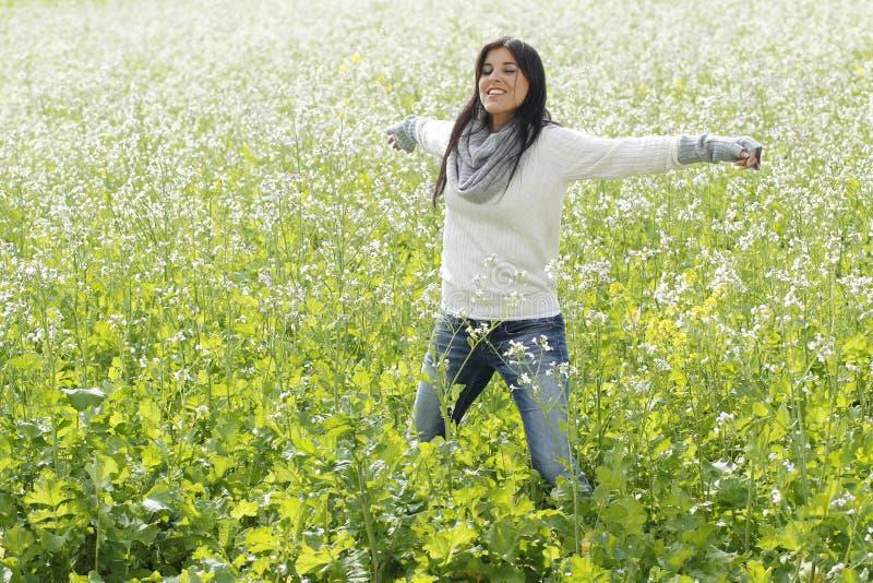 Gelukkige vrouw in aard met uitgestrekte wapens op een bloemgebied royalty-vrije stock foto