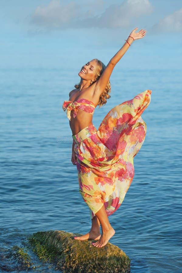Gelukkige vrouw bij de kust stock foto's