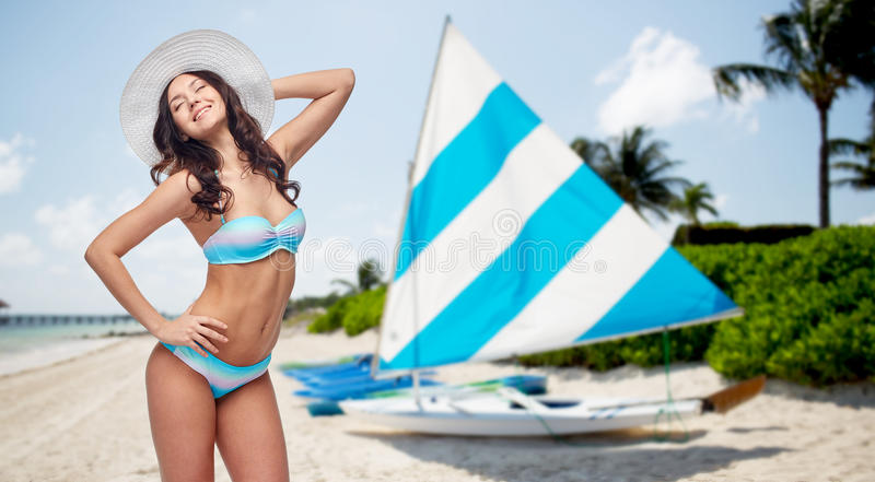 Gelukkige vrouw in bikini en zonhoed op strand stock fotografie