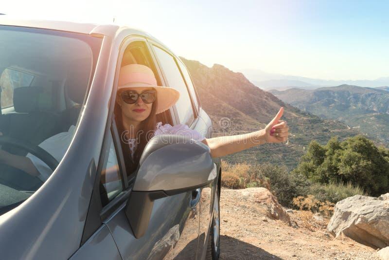 Gelukkige vrouw binnen auto het drijven in de straat stock foto's