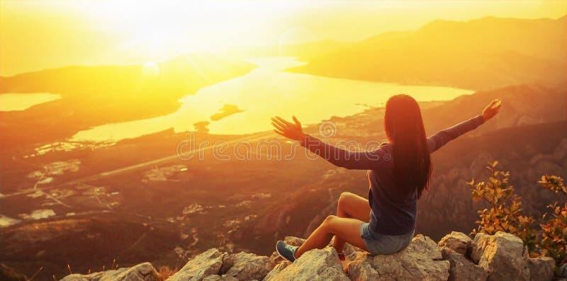 Gelukkige vrouw in de bergen die de zonsondergang bekijken stock afbeeldingen