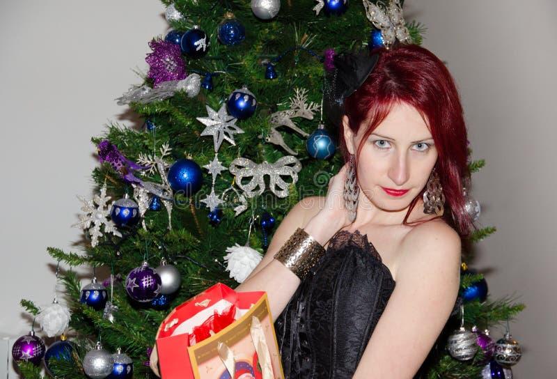 Gelukkige vrouw dichtbij een Kerstboom stock foto's